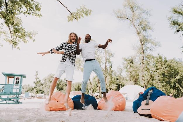 Afrykańscy i kaukascy przyjaciele ma zabawę na plaży