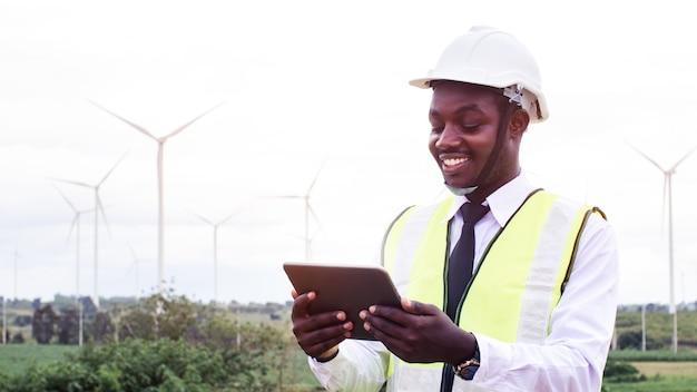 Afrykańscy inżynierowie pracujący na miejscu ze śmigłem turbiny wiatrowej i jasnym błękitnym niebem w tle. energia alternatywna, przyjazna środowisku w przyszłości. innowacja w zakresie czystej energii