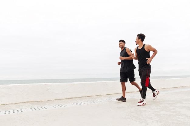 Afrykańscy sportowi mężczyzna przyjaciele biega outdoors