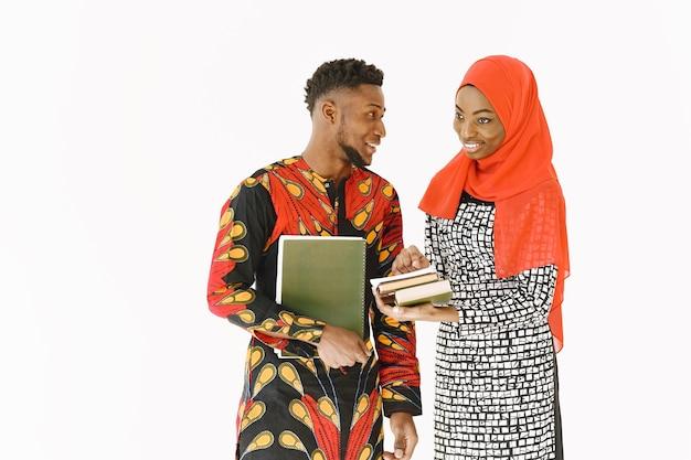 Afrykańscy studenci. młodzi ludzie w tradycyjnych nigeryjskich strojach. trzymanie książek. koncepcja badania.