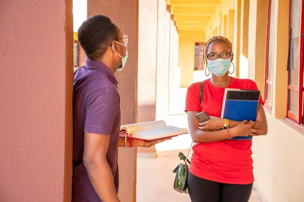Afrykańscy studenci w kampusie szkolnym noszący maski na twarz