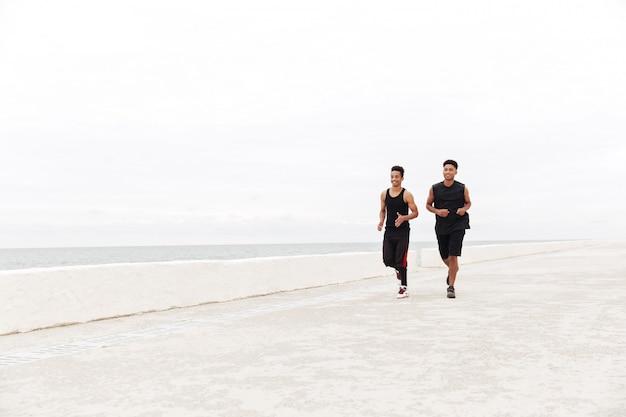 Afrykańscy szczęśliwi sportów mężczyzna przyjaciele biega outdoors