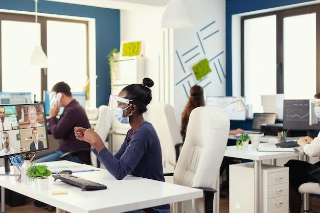 Afrykańska bizneswoman nosząca bezprzewodowe słuchawki podczas rozmowy online z ludźmi biznesu noszącymi maskę na twarz. nowe normalne biuro biznesowe wieloetniczny zespół pracujący z poszanowaniem dystansu społecznego na całym świecie