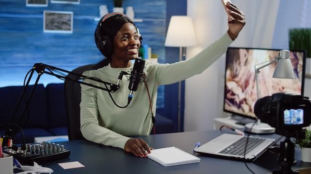 Afrykańska blogerka, portret vlogera robiąca sobie zdjęcia na smartfonie