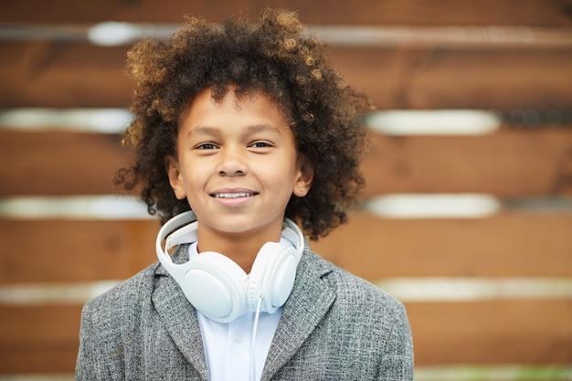 Afrykańska chłopiec z hełmofonami outdoors