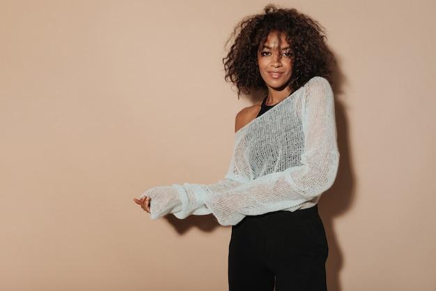 Afrykańska dama z brunetką w stylowej bluzce, białym swetrze i czarnych spodniach, patrząc w kamerę na izolowanej ścianie...