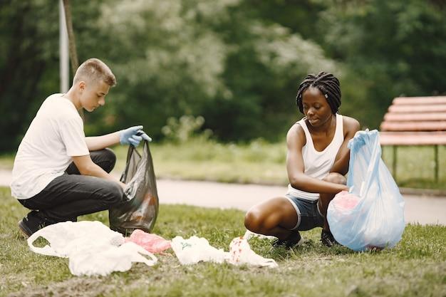 Afrykańska dziewczyna i europejski chłopak zbierają śmieci. aktywiści oczyszczający park na boki.