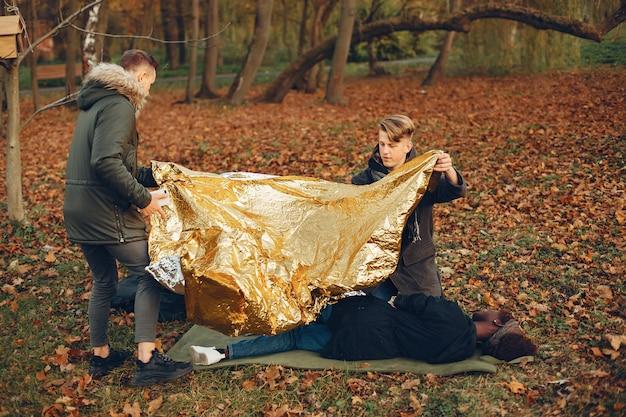 Afrykańska dziewczyna jest owinięta ciepłą folią ochronną. faceci pomagają kobiecie. udzielanie pierwszej pomocy w parku.
