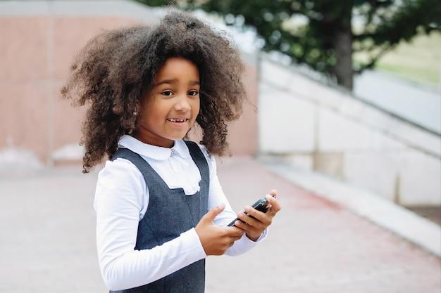 Afrykańska dziewczyna nastolatka z lokami ze smartfonem w dłoniach.