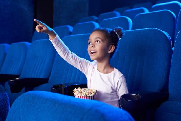Afrykańska dziewczyna poiniting z palcem przy ekranem w kinie.