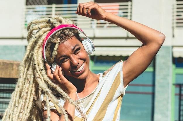 Afrykańska dziewczyna rusza się blond dredy włosiany jest ubranym podczas gdy słuchający muzyczną listę odtwarzania z hełmofonami