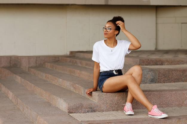 Afrykańska dziewczyna w białej koszulce i okularach siedzi na schodach. lato