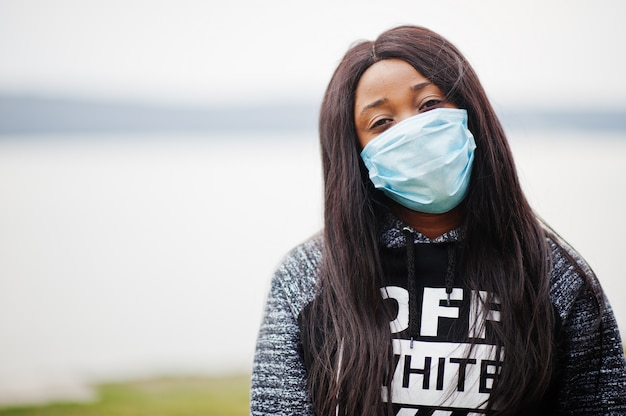Afrykańska dziewczyna w parku w medycznych maskach chroni przed infekcjami i chorobami kwarantanna wirusa koronawirusa.