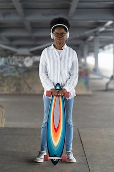 Afrykańska dziewczyna z deskorolką modna kobieta ubrana w miejski strój nosi słuchawki trzyma longboard