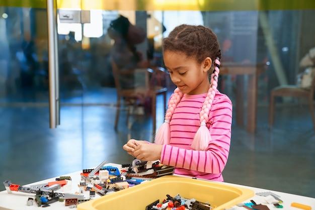 Afrykańska dziewczyna za pomocą zestawu budowlanego