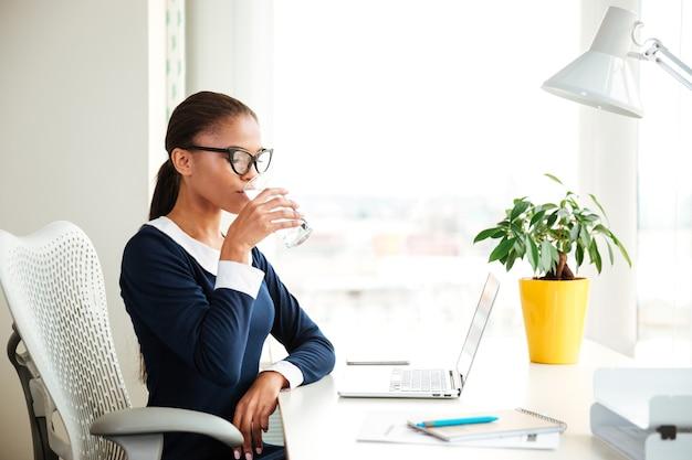 Afrykańska kobieta biznesu w sukience siedzi na fotelu i pije wodę w biurze
