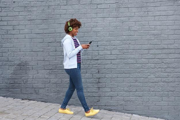 Afrykańska kobieta chodzi i słucha muzyka na telefonie komórkowym