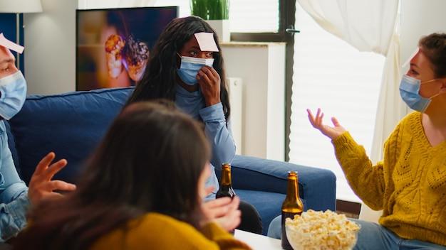 Afrykańska kobieta gra w grę imienia z karteczkami samoprzylepnymi na czole, bawiąc się z przyjaciółmi podczas nowej normalnej imprezy. noszenie maski na twarz w salonie, zachowując dystans społeczny, aby zapobiec rozprzestrzenianiu się wirusa