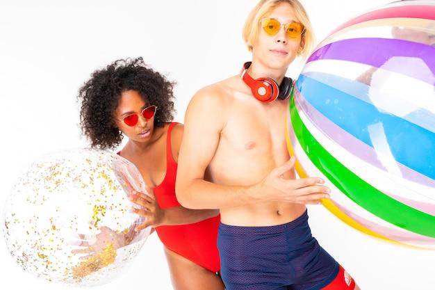 Afrykańska kobieta i kaukaski blondynka mężczyzna stoi w strój kąpielowy z dużymi gumowymi piłkami i uśmiechami, na białym tle na białej ścianie