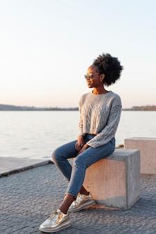 Afrykańska kobieta jest ubranym okulary przeciwsłonecznych i patrzeje daleko od