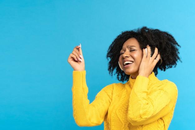 Afrykańska kobieta, milenials, słuchająca muzyki, nosi słuchawki bezprzewodowe, śpiewa i tańczy w studio