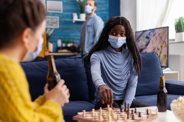 Afrykańska kobieta nosząca maskę gra w szachy z przyjaciółmi, utrzymując dystans społeczny, rozmawiając o zabawie, pijąc piwo zapobiegając rozprzestrzenianiu się wirusa covid. gry planszowe, rywalizacja, taktyka, aktywność.