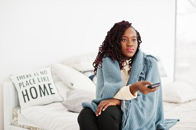 Afrykańska kobieta ogląda telewizję w domu i trzyma pilota na łóżku