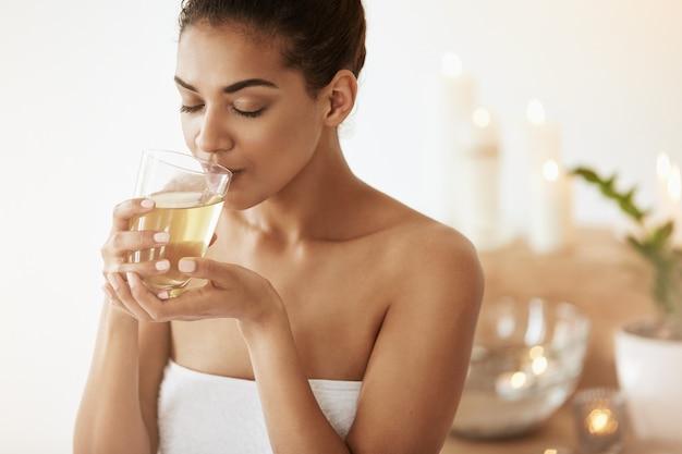 Afrykańska kobieta pije zielonej herbaty odpoczywa w salonie spa.