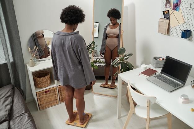 Afrykańska kobieta plus size stojąca na wadze w sypialni