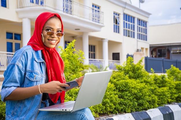 Afrykańska kobieta siedząca na zewnątrz z laptopem i telefonem, dokonująca płatności online