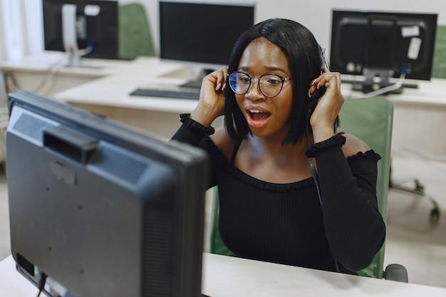 Afrykańska kobieta siedzi w klasie informatyki. pani w okularach. kobieta student siedzi przy komputerze.