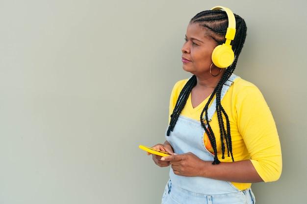 Afrykańska kobieta słucha muzyki i korzysta ze smartfona, stojąc na szarym tle.