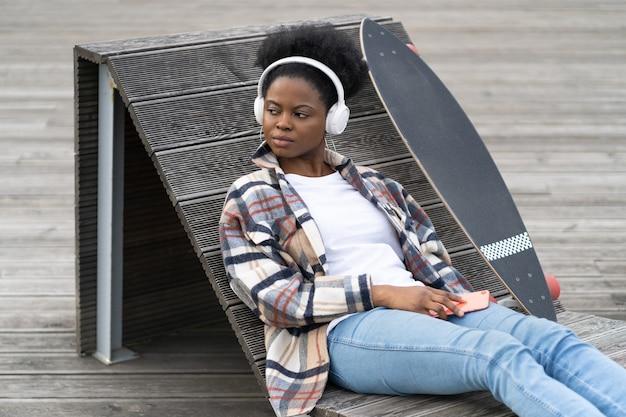 Afrykańska kobieta słucha muzyki na zewnątrz, nosi codzienne ubrania z deskorolką, siedzi na ławce w przestrzeni miejskiej