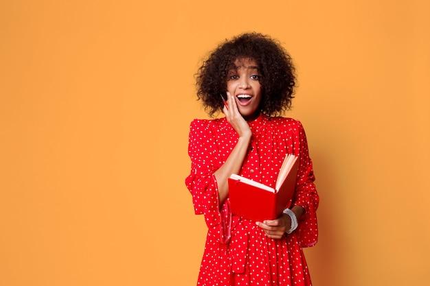 Afrykańska kobieta trzyma notatnik z twarzą niespodzianka.