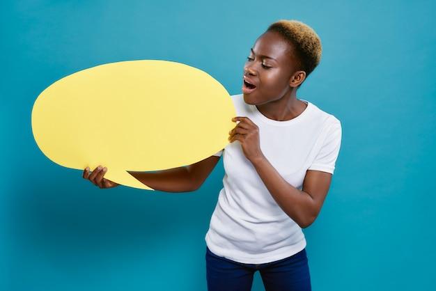 Afrykańska kobieta trzyma żółtego mowa bąbel w formie owalu.