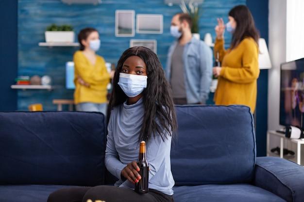 Afrykańska kobieta utrzymująca dystans społeczny nosząca maskę na twarz podczas spotkania z przyjaciółmi, aby zapobiec rozprzestrzenianiu się koronawirusa trzymającego butelkę piwa, patrząc na kamerę siedzącą na kanapie. obraz koncepcyjny.