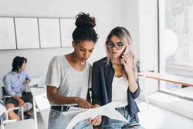Afrykańska kobieta w białej koszulce znalazła błąd w raporcie. zmartwiona pracownica biura dzwoni do współpracownika, aby rozwiązać problemy w pracy, podczas gdy jej współpracownicy wykonują swoją pracę.