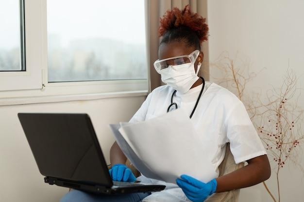 Afrykańska kobieta w medycznej odzieży przy stole z dokumentami i laptopem
