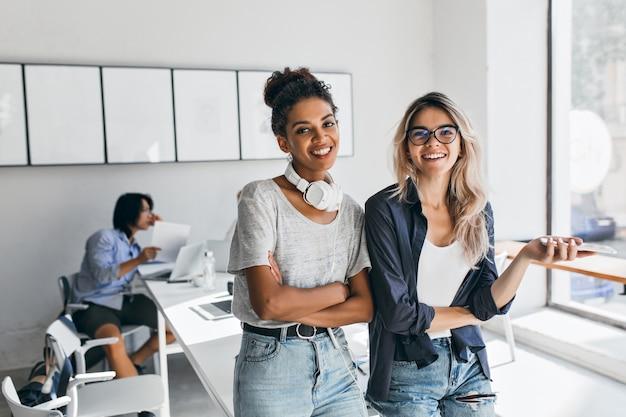 Afrykańska kobieta w modnym, codziennym stroju przyszła do biura przyjaciela i pozowała z azjatyckim programistą. urocza blond sekretarka bawi się podczas przerwy, podczas gdy jej japoński kolega pracuje.