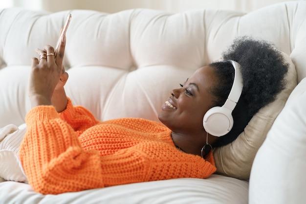 Afrykańska kobieta w swetrze nosi słuchawki, słuchając muzyki, używając smartfona, leżąc na kanapie w domu