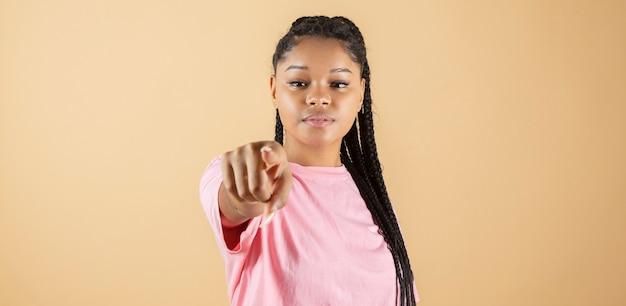 Afrykańska kobieta wskazująca palcem na aparat, poważna twarz, żółte tło