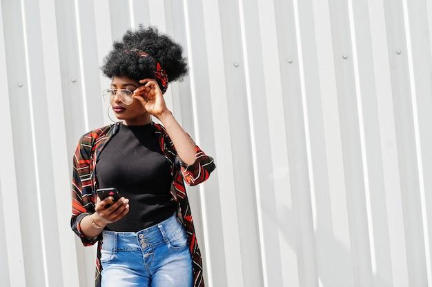 Afrykańska kobieta z afro włosami, w jeansowych szortach i okularach postawionych na białej stalowej ścianie z telefonem w ręku.