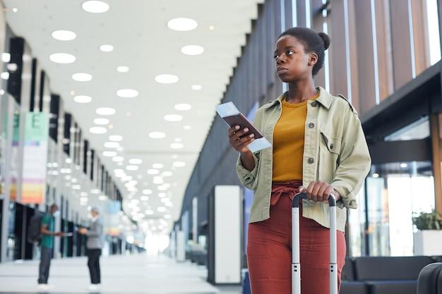 Afrykańska kobieta z bagażem i biletami stojąc na lotnisku i czekając na swój lot
