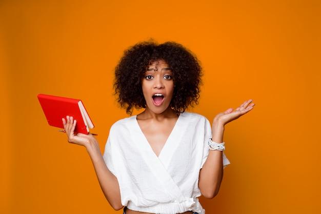 Afrykańska kobieta z niespodzianki twarzy mienia notatnikiem. śmieszne emocje.