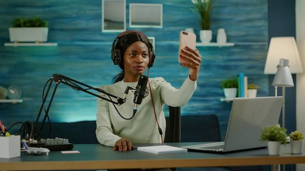 Afrykańska kobieta za pomocą smartfona biorąc selfie w odcinku nagrywania biznesu rozrywkowego. podcast internetowy na żywo z produkcji online pokazuje hosta transmitującego treści na żywo, nagrywającego cyfrowe media społecznościowe.