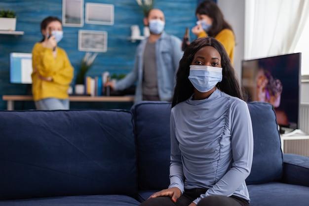 Afrykańska kobieta zachowująca dystans społeczny, nosząca maskę na twarz podczas spotkania z przyjaciółmi, aby zapobiec rozprzestrzenianiu się koronawirusa, trzymająca butelkę piwa, patrząc na kamerę siedzącą na kanapie, epidemia covid 19