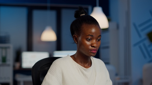 Afrykańska księgowa pracuje w nadgodzinach obliczając zysk calculating