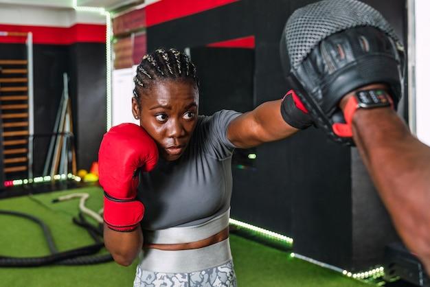 Afrykańska lekkoatletka uprawiania boksu z trenerem na siłowni. kobieta w stroju sportowym na siłowni uderza w rękawice bokserskie w rękach swojego instruktora