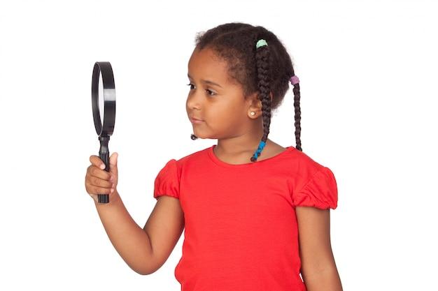 Afrykańska mała dziewczynka patrzeje przez powiększać - szkło
