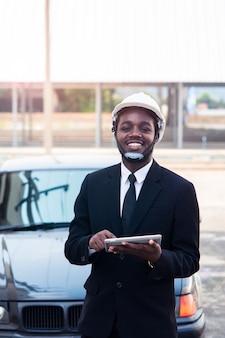 Afrykańska mężczyzna inżyniera budowy pracownika pozycja i use teblet z samochodem